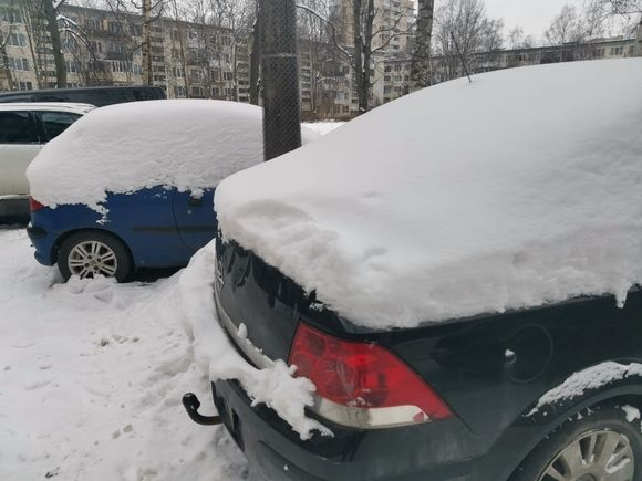 В Петербурге рабочие счистили снег с крыши дома на припаркованную машину