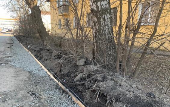В Курске новый асфальт кладут у старых кустарников