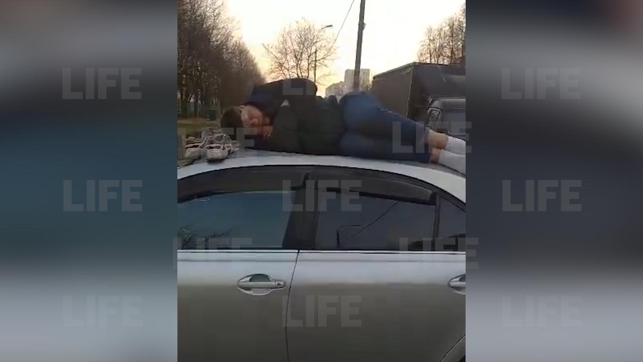 'С какой бы стороны его скинуть': В Москве пьяный мужчина уснул на крыше чужого автомобиля — видео